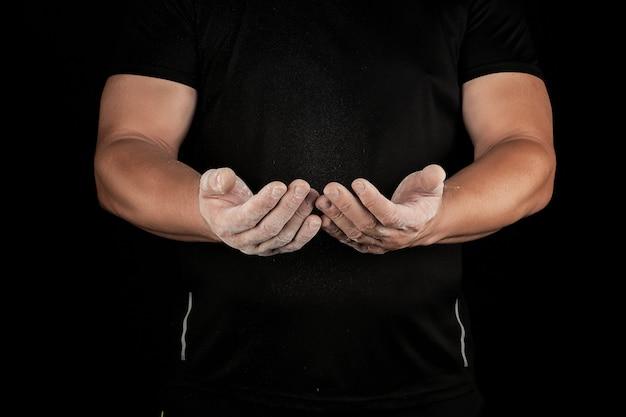 Atleta do sexo masculino adulto esfrega pó branco com magnésia antes de eventos esportivos