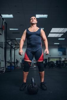 Atleta do sexo masculino se prepara para exercícios com kettlebell