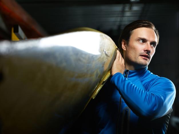 Atleta do sexo masculino se preparando para a navegação. jovem atraente homem branco com uma jaqueta de natação azul carregando um barco e olhando para o lado