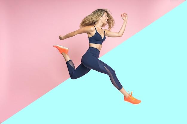 Atleta e corredor de uma linda mulher está pulando suspenso no ar