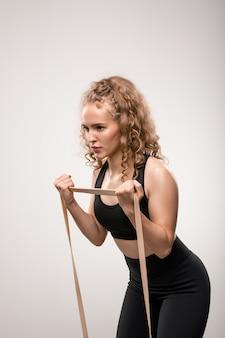 Atleta em forma de treino preto dobrando-se ligeiramente para a frente enquanto faz exercícios para o braço e usando uma faixa flexível durante o treino