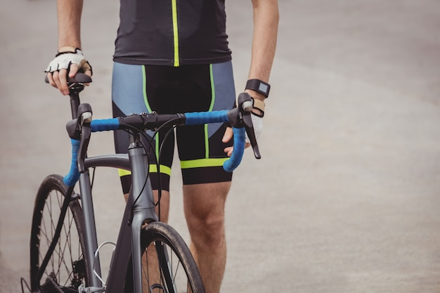 Atleta em pé com sua bicicleta