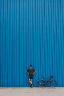 Atleta em roupas esportivas posando com uma bicicleta preta perto da parede azul
