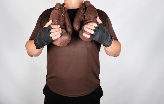 Atleta em roupas marrons detém muito velhas luvas de boxe de couro vintage