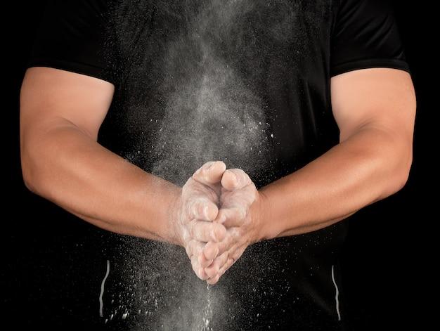 Atleta em roupas pretas batendo palmas, magnésio branco talco voar para longe