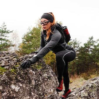 Atleta esportiva feminina caminhando com cuidado sobre pedras