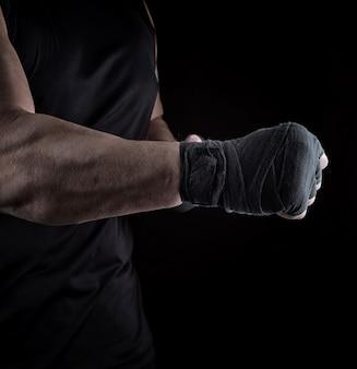 Atleta está de pé com um braço esticado enfaixado