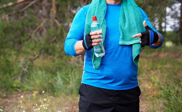 Atleta está de pé no meio da natureza em um uniforme azul com uma toalha verde
