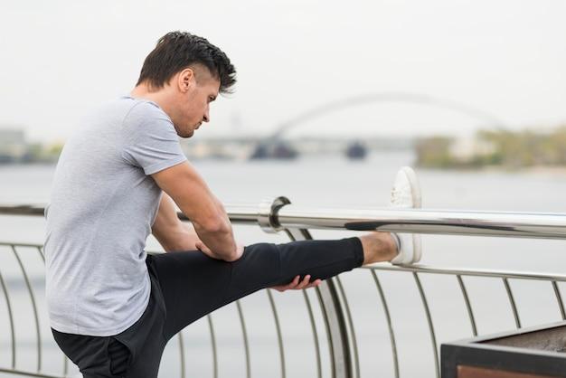 Atleta, estendendo-se ao ar livre antes de correr