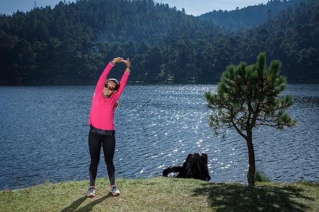 Atleta estirando depois de correr a la orilla de um lago