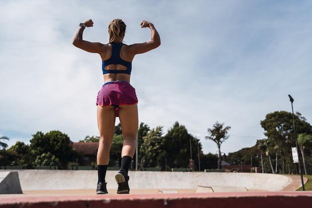 Atleta exibindo os músculos das costas ao ar livre.
