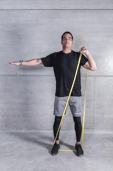 Atleta fazendo exercício com elástico de borracha