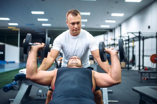 Atleta fazendo exercícios sob o controle do instrutor