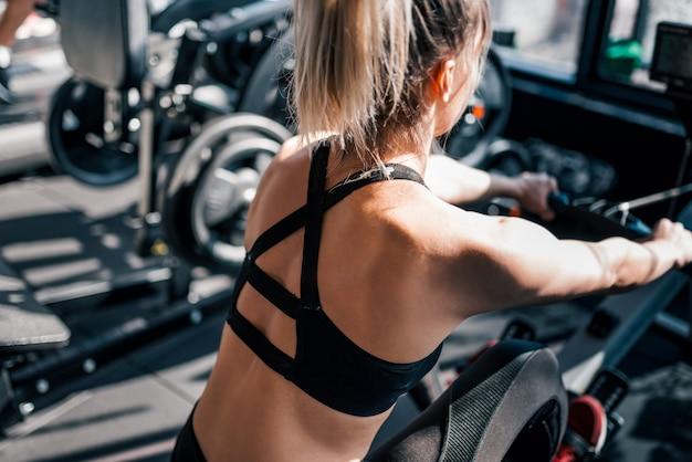 Atleta fêmea que exercita na máquina de enfileiramento no gym, close-up.