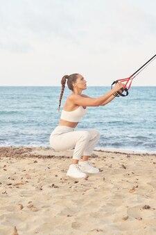 Atleta feminina agachada durante o treinamento de suspensão na praia
