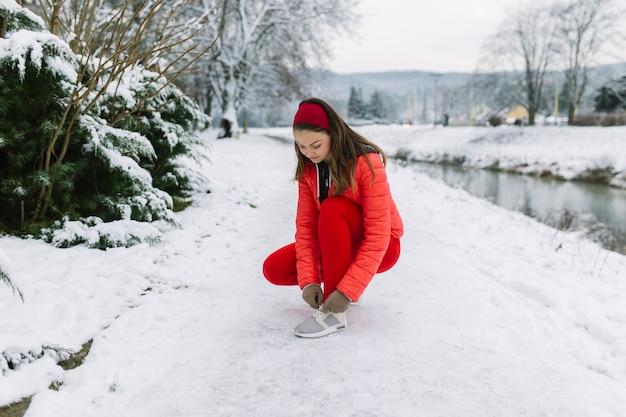 Atleta feminina, amarrando o cadarço perto do lago no inverno