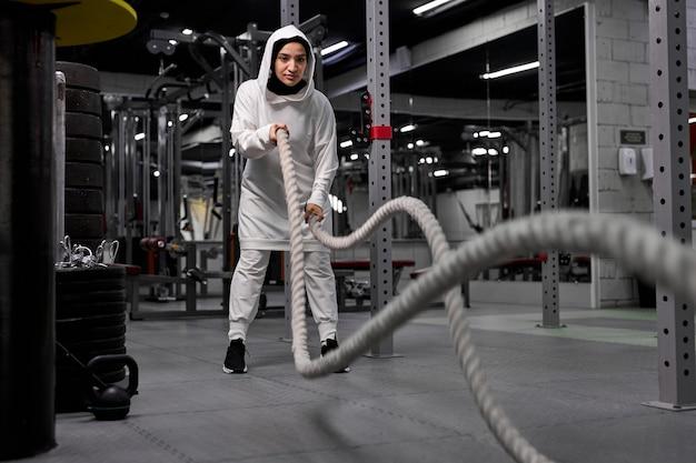 Atleta feminina árabe fazendo exercícios de crossfit com corda de batalha, usando hijab esportivo. esportes regulares estimulam o sistema imunológico e promovem uma boa saúde. estilo de vida saudável
