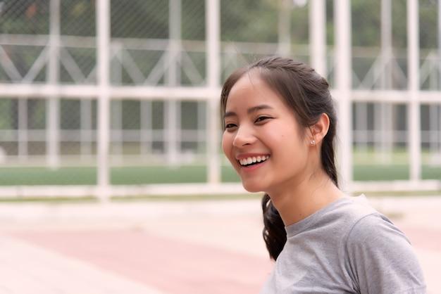 Atleta feminina asiática que tem boa pele sorrindo alegremente após o exercício.