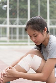 Atleta feminina asiática, sentado ao lado do estádio. ela teve uma lesão no joelho e conseguiu seus primeiros socorros.