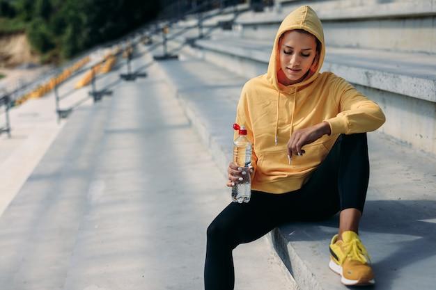 Atleta feminina atraente com capuz na cabeça de suéter amarelo relaxante nos degraus com uma garrafa de água e olhando para baixo.