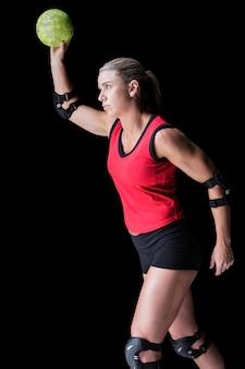 Atleta feminina com almofada de cotovelo jogando handebol no preto