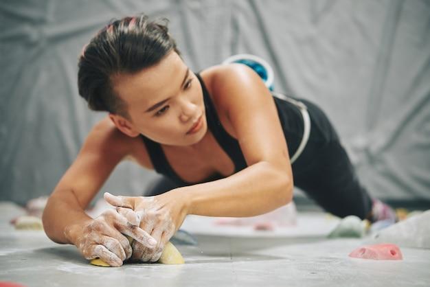 Atleta feminina com as mãos cobertas por magnésio alimentado segurando uma pedra artificial na parede de pedregulho
