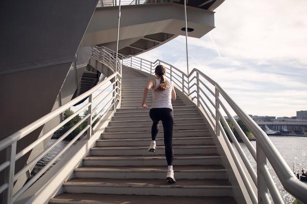 Atleta feminina correndo escada rolante