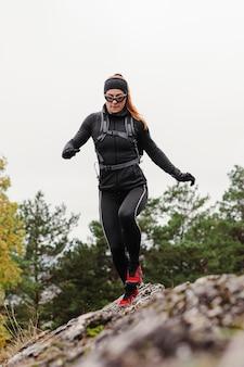 Atleta feminina correndo sobre pedras