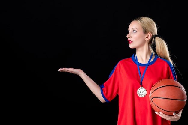 Atleta feminina de basquete com bola e medalha de ouro em fundo preto.