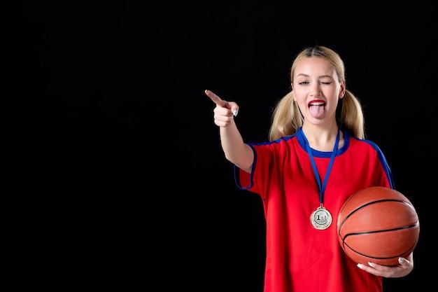 Atleta feminina de basquete com bola e medalha de ouro no fundo preto vencedor do troféu