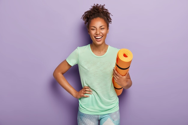 Atleta feminina de pele escura, alegre e saudável mantém a mão no quadril, segura o colchonete enrolado, está em boa forma física, faz treinamento esportivo todos os dias, usa camiseta e leggings. pessoas, ioga