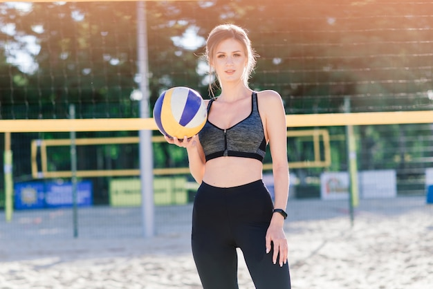 Atleta feminina de vôlei de praia com bola na quadra de vôlei