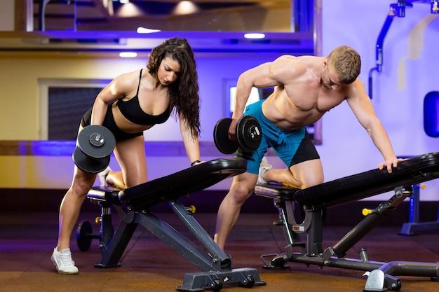 Atleta feminina e atleta masculino treinando juntos na academia
