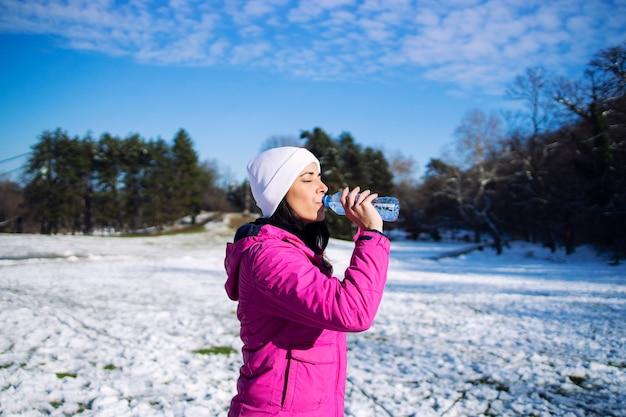 Atleta feminina em roupas de inverno, bebendo água antes de treinar na neve.