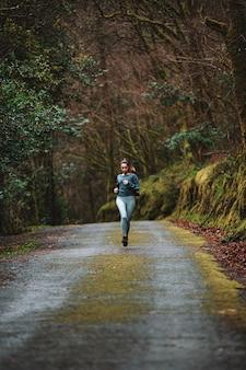 Atleta feminina em roupas esportivas, correndo ao longo de uma estrada de asfalto na floresta durante o treinamento cardiovascular