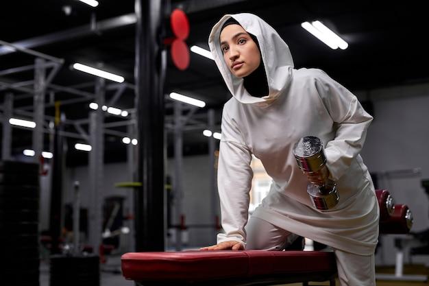 Atleta feminina em treinamento de hijab com halteres no moderno centro de fitness, jovem muçulmana está cheia de energia e poder. motivação, estilo de vida saudável e conceito de esporte