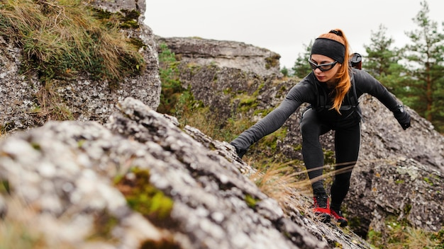 Atleta feminina esportiva escalando pedras, vista frontal