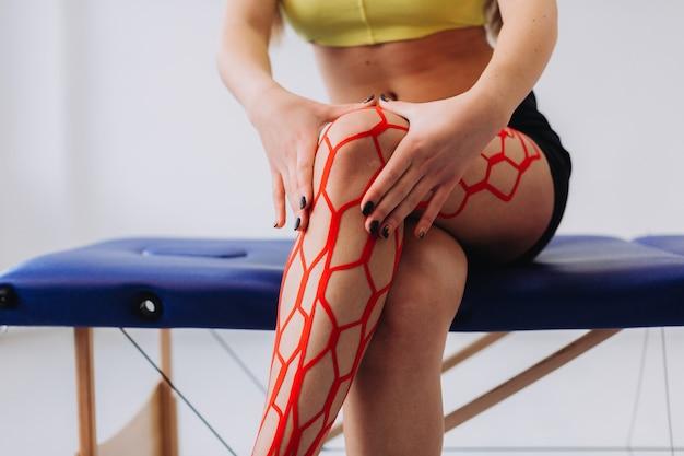 Atleta feminina esportiva jovem segurando a perna ferida após tratamento com fita kinesio.