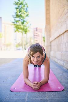 Atleta feminina, exercitando-se fora da cidade, em um tapete rosa. vestindo sutiã azul e roupa esportiva roxa.