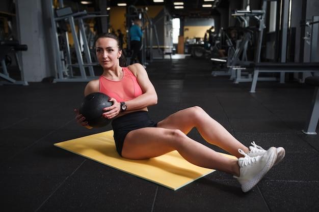 Atleta feminina fazendo torção russion, segurando uma bola medicinal