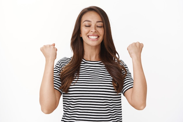 Atleta feminina feliz e aliviada recebendo resultados esportivos, sentindo-se realizada e satisfeita, erguendo os punhos, respirando feliz e sorrindo, triunfando, celebrando o sucesso, vencendo a competição
