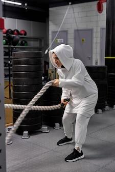 Atleta feminina mulçumana de crossfit em hijab, malhando com cordas pesadas, parecendo determinada e concentrada.