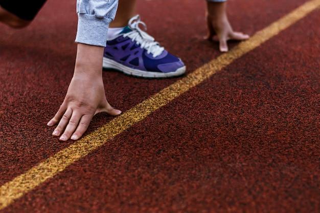Atleta feminina na linha de partida de uma pista do estádio se preparando para uma corrida