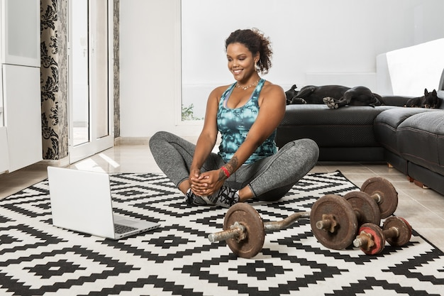 Atleta feminina negra alegre vestindo roupas esportivas, sentada no chão e esticando as pernas enquanto assiste a uma aula online durante o treino em casa com cachorros