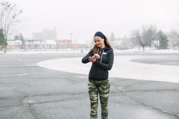 Atleta feminina olhando o tempo durante o exercício na rua