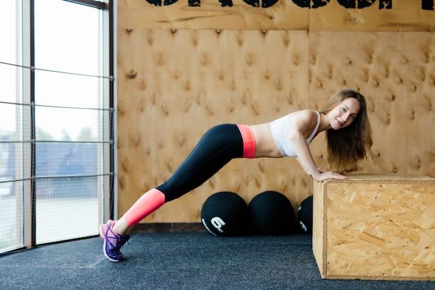 Atleta feminina praticando flexões e burpees na academia