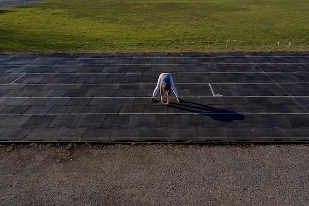 Atleta feminina, preparando as pernas para o treino cardio. corredor de fitness fazendo a rotina de aquecimento.