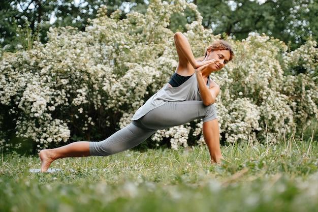 Atleta feminina realiza exercícios de ioga ao ar livre com uma árvore florida em pé na grama
