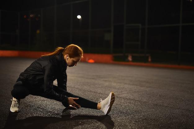 Atleta feminina ruiva motivada, esticando as pernas para se aquecer antes de fitness urbano e corrida sem ...