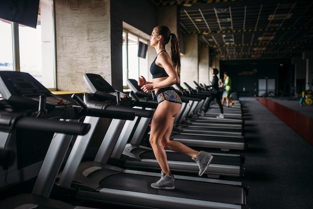 Atleta feminina se exercitando na esteira em um ginásio de esportes